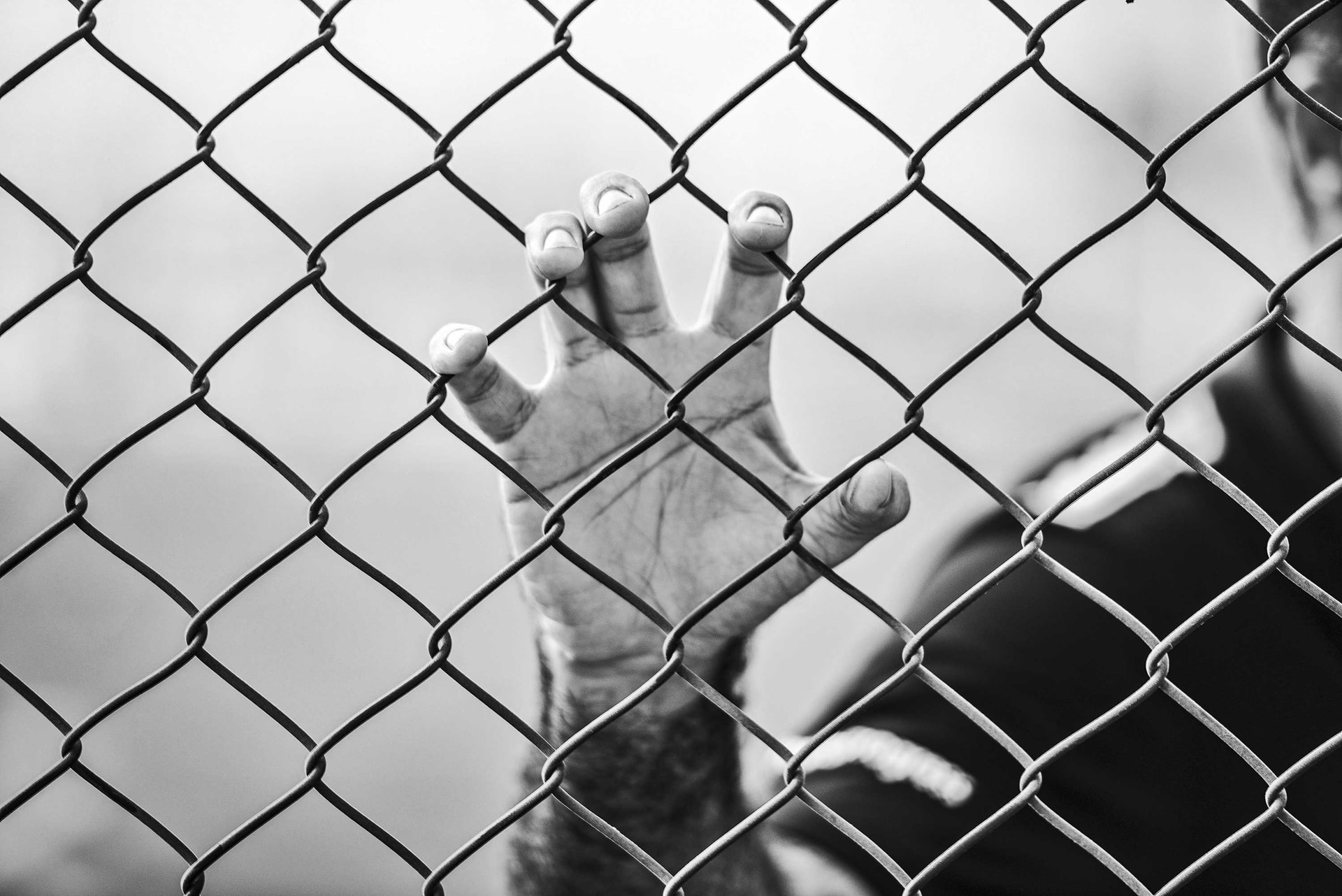 This is a black and white image of a hand gripping a chain link fence