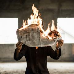 man reading newspaper on fire
