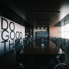 """an empty boardroom with """"Do Good Things"""" printed on a feature wall"""