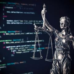 lady justice in front of a computer screen