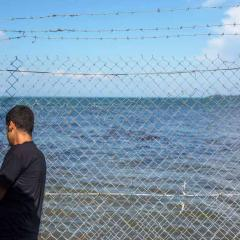 An asylum seeker stands behind a wire fence overlooking the ocean