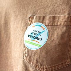 """brown shirt with an """"I've been vaccinated"""" sticker on it."""
