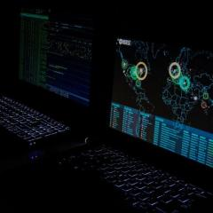 computer screens in dark showing world map data with cyrberattacks